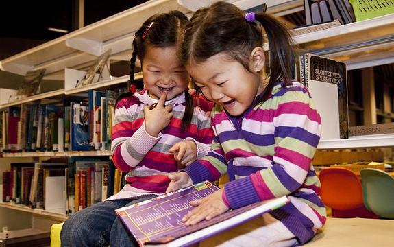 Foto av to små jenter med musefletter og stripete, fargerike gensarar, som sit og ser i ei bok på eit bibliotek. Foto: Alexander Klanderud, Kongsvinger kommune/www.flickr.com