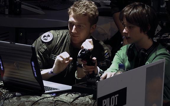 Foto frå dokumentarfilmen Drone. Vi ser ein amerikansk soldat og ein ung gut som sit framføre ein pc og spelar dataspel. Pressefoto.