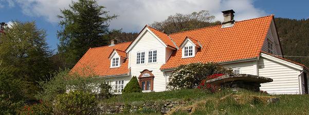 Foto av det store, kvite hovudhuset på den freda futegarden Alværn i Lavik.