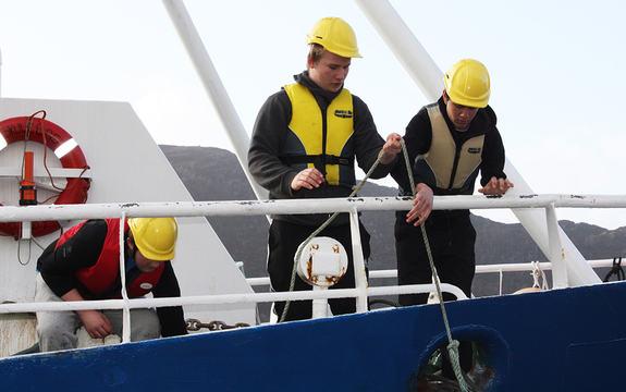 Foto av tre elevar ombord på opplæringsfartøyet Skulebas. Foto: Måløy vidaregåande skule