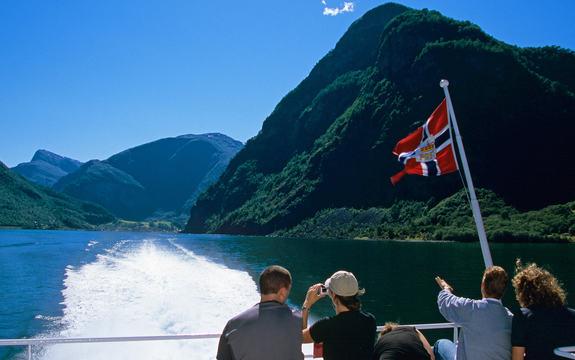 Nærøyfjorden sett frå båt, med turistar og det norske flagg.