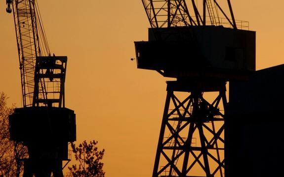 Industrikraner i silhuett mot solnedgang