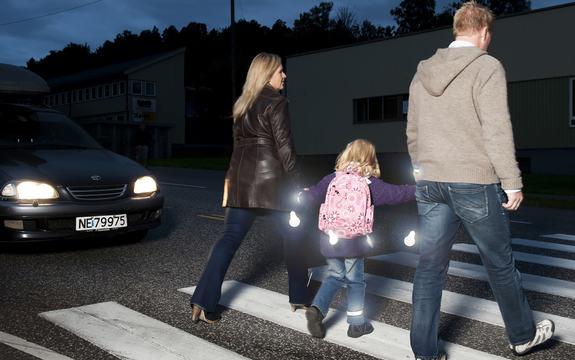 Ein familie på veg over gata ein mørk kveld, med refleksar som lyser opp