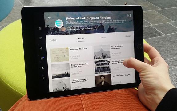 Bilete av at nokon ser på historiske bilete frå Fylkesarkivet i Sogn og Fjordane på ein iPad.