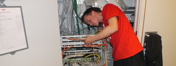 Gut som arbeider med kablar i nettverksskåp.