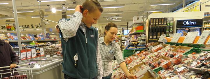 Gut i arbeid på butikk får instruksjon av tilsett i butikk med frukt og grønt.