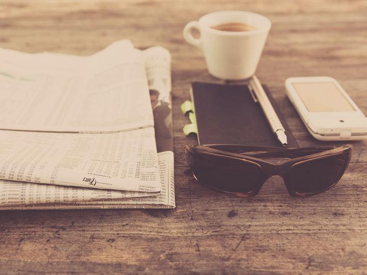avis, kaffekopp, notisblok, blyant, mobil og solbriller ligger på bordet