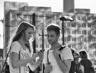 Ei jenta og ein gutt med mobilen