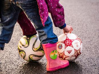 Beiner til eit barn som spiller med to ball