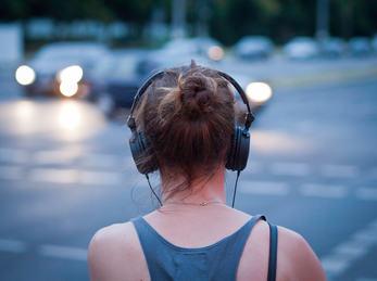 Kvinne med hodetelefon på vegkryss