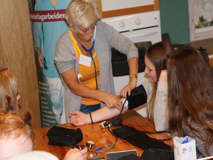 Lærar målar blodtrykk på ein elev.