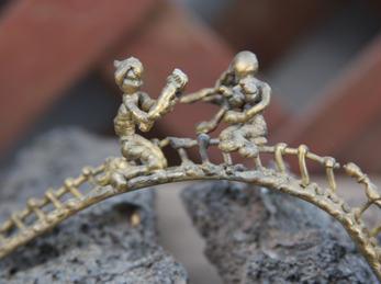 Miniaturkunst av metal, to menesker på brua