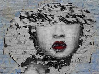Ansikt av graffiti som oppløser seg frå veggen