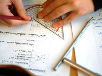 hender som tekner med vinkelhake på papir med øvelser