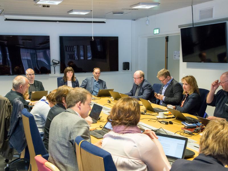 Politikarar og ansatte rundt eit møtebord