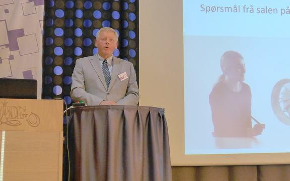 Jan Heggheim på talarstol med projisert bilete til venstre for han
