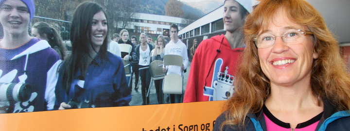 Venke Nordeide foran plakat