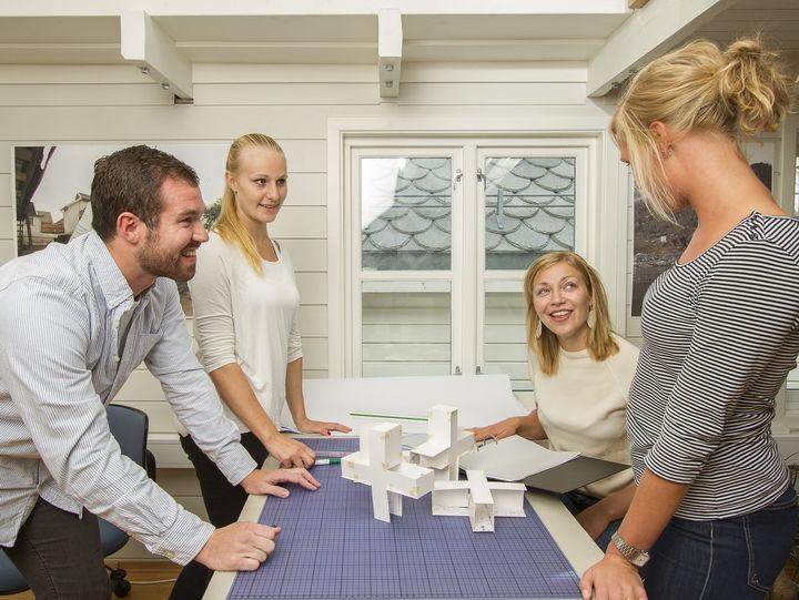 Fire unge menneske samla rundt eit bord med papirmodellar føre seg