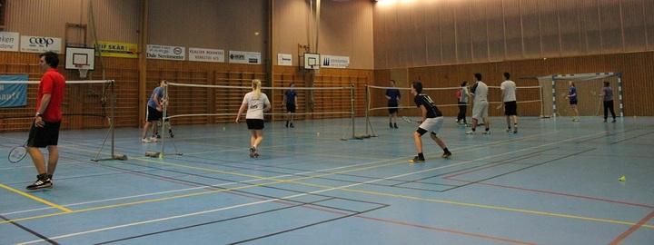 Elevar spelar badminton i hallen.