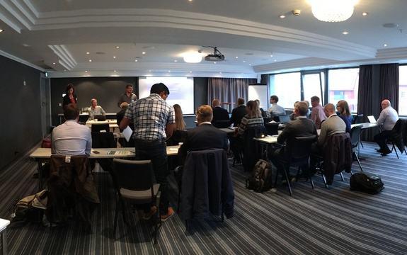 Samling menneske i seminar-samanheng med to-tre per bord