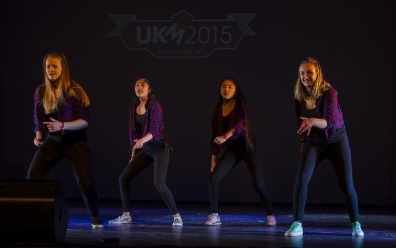 Fire jenter i like klede som dansar på ei mørk scene