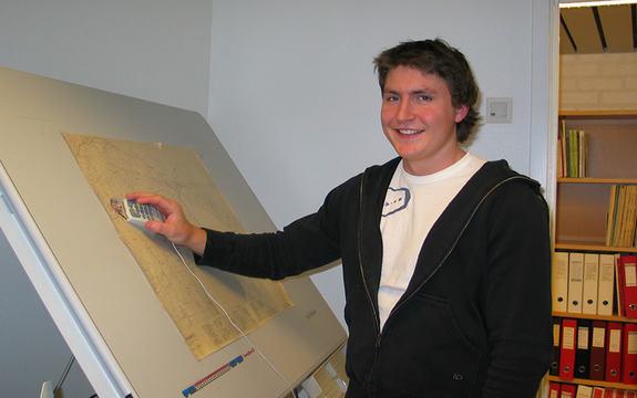 ung mannleg tilsett, Tor Mikkel Tokvam, står ved digitaliseringsbord og legg stadnamn inn på kart