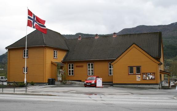 Gult trehus med norsk flagg foran