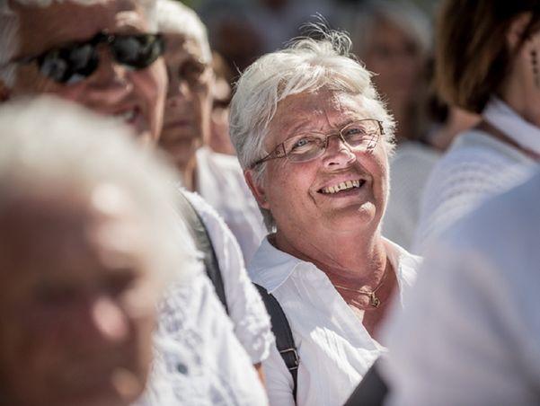 Kvinne i folkemengde smilar