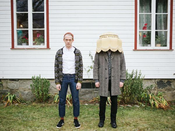 To menn står foran eit kvitt hus og ser mot kamera, den eine har ein lampeskjerm over hovudet