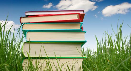 Bilder av bøker på ei grøn eng