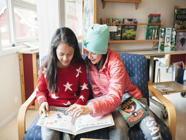 To jenter omlag 11 år gamle sit i lag i sofa på eit bibliotek og les i ei opa bok med barneteikningar, to lukka bøker på fanget