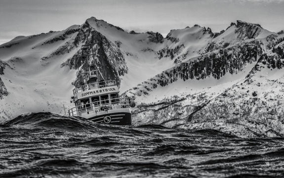 Svart-kvitt bilete av fiskebåt i bølgar med snøkledde fjell i bakgrunnen