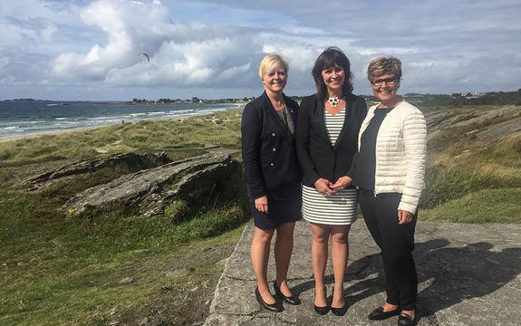 Tre kvinner står foran ei strand og eit hav med blå himmel og kvite skyar.