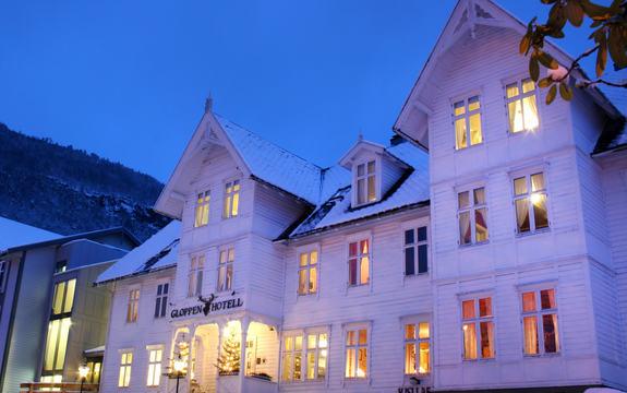 Gloppen hotell sett om natta med snødekte tak og lys i vindauga