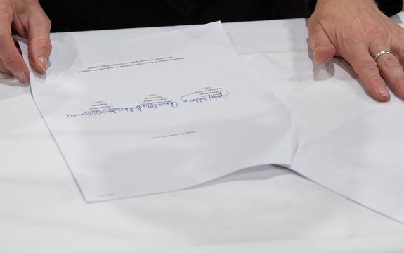 Ark med signaturar på eit bord
