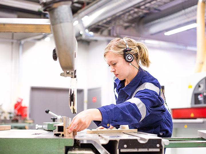 Elev i arbeid ved maskinene på treverkstad