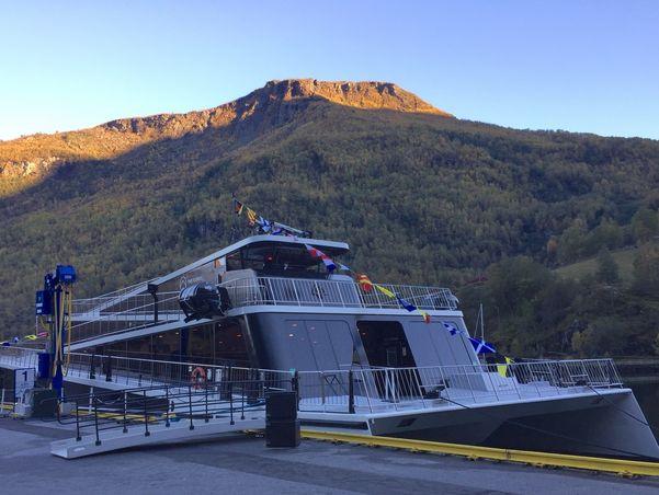 Moderne båt ved kai i ein fjord