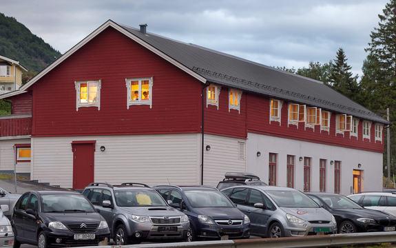 Raudt stort hus med parkering med bilar i framgrunn