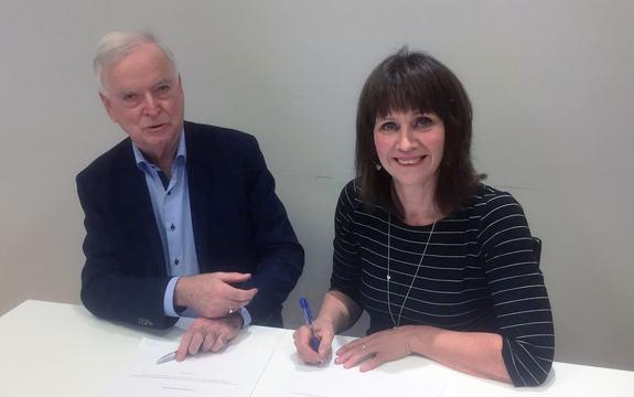 Mann og kvinne ved bord signerer avtale