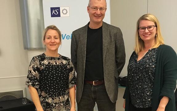 Foto av Eline Orheim, Carlo Aall og Ida-Beate Mølmesdal. Dei står framfor ein plakat med bokstavane KS.