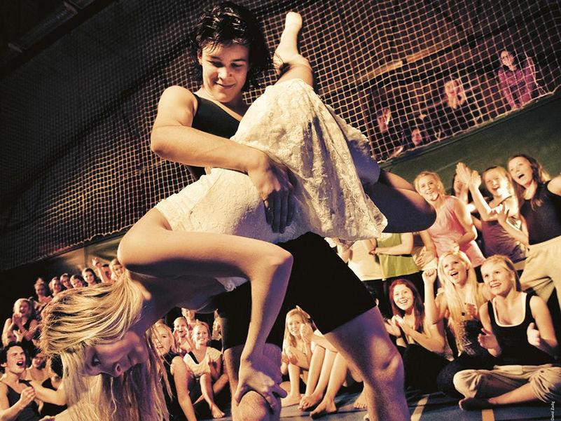 Foto som syner ei jente og ein gut som dansar. Guten er kledd i svart og held jenta, som er kledd i kvitt, opp-ned. Bak dei ser me ungdomar som er publikum.