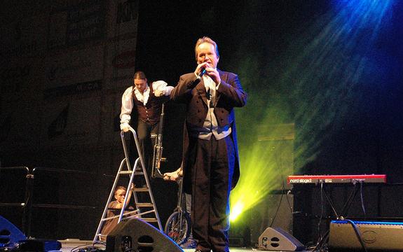 Sirkusdirektør Jan Ketil Smørdal på scena i smoking. Han står med ein mikrofon, og bak han står ein artist som er på veg opp på ein einhjulssykkel. Det er mørkt på scena, med eit sterkt grønt lys i bakgrunnen.