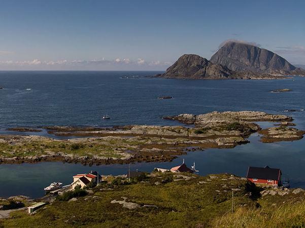 Foto som er teke på øya Skorpa i Flora. Vi ser mot Batalden og det open havet. Det er grønt gras og lettskya, men blå himmel.