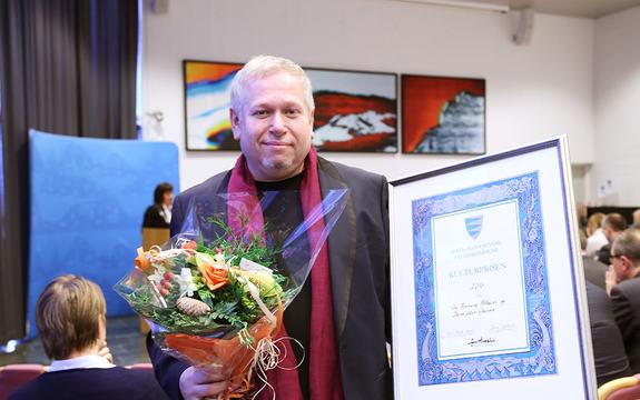 Foto av Ove Henning Solheim, som tok imot fylkeskulturprisen 2016 på vegne av seg sjølv og Dans Uten Grenser. Han held ein blomsterbukett i ei hand og diplomet for prisen i den andre. Bak han ser vi ein fullsett fylkestingssal.