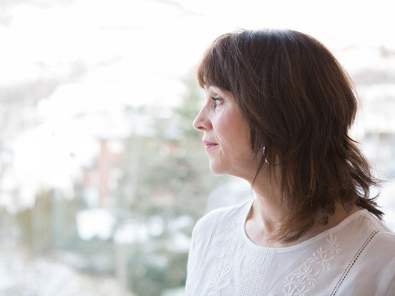 Foto av fylkesordførar Jenny Følling som skodar ut av eit vindauga. Følling har håret hengjande laust og har på seg ein kvit gensar.