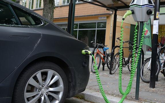 Foto av elbil som er tilkopla hurtigladestasjon ei ei brusteinslagt gate. Bilen er mørk grå, og ladekabelen er grøn.