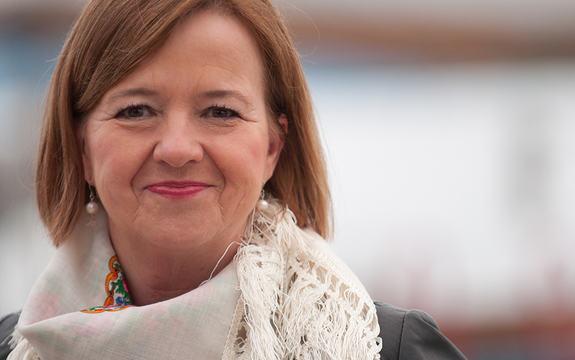 Portrettfoto av Tone Winje som er styreleiar for Førdefestivalen. Ho har på seg svart skinnjakke og kvitt skjerf. Det lysebrune håret heng laust og ho har på kvite perleøyredobbar og rosa leppestift.