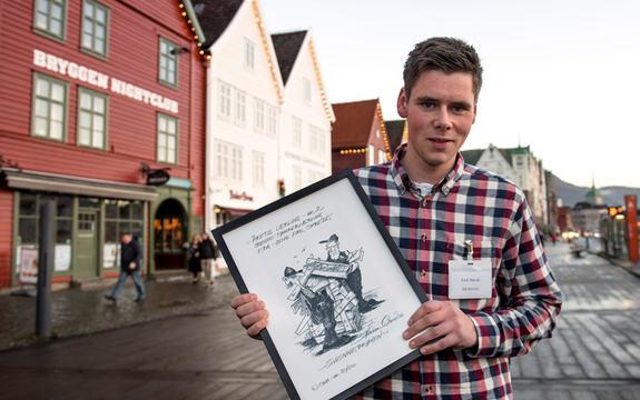 Foto av årets tømrarlærling, Emil Skrede, fotografert på Bryggen i Bergen. Skrede har på seg rutete skjorte og held opp diplomet han har fått.