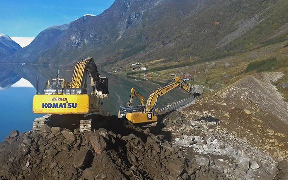 Foto frå arbeidet på Lindeskreda på Veitastrondsvegen. To gule gravemaskiner er i ferd med å bygga ein svær rasvoll. Det er sommar, blå himmel og stille på Veitastrondsvatnet. I bakgrunnar skimtar vi Jostadalsbreen.