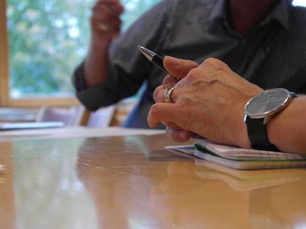 Bilete av hender som held ein penn